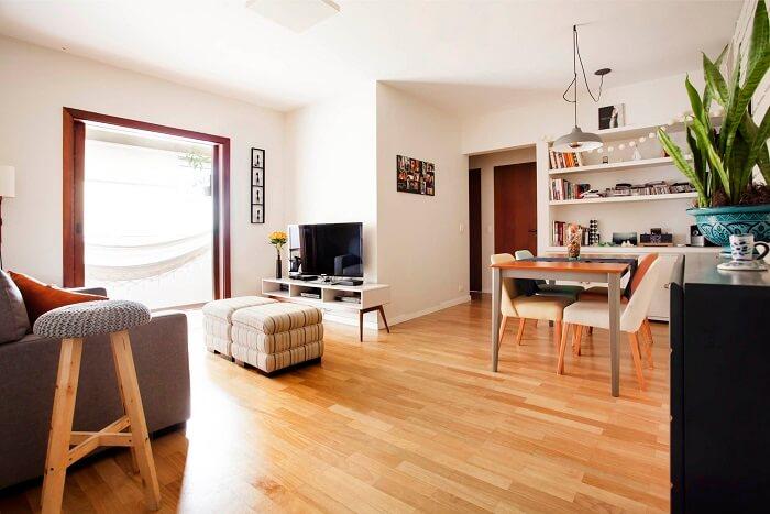 O piso laminado de madeira integrou os ambientes de sala de estar e sala de jantar