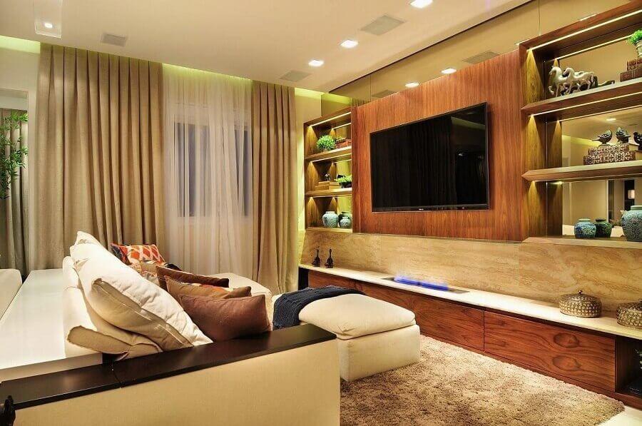 painel com rack de madeira para sala decorada em tons neutros com iluminação de led em prateleiras Foto Quitete Faria
