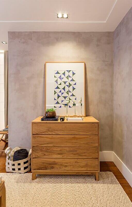 quarto decorado com cômoda de madeira e parede de cimento queimado