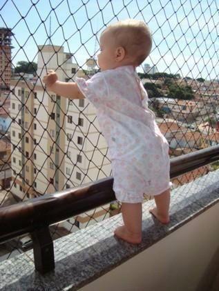 redes de proteção - criança segurando rede de proteção