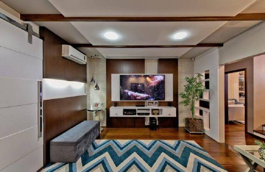 sala ampla decorada com rack com painel branco Foto Espaço do Traço Arquitetura