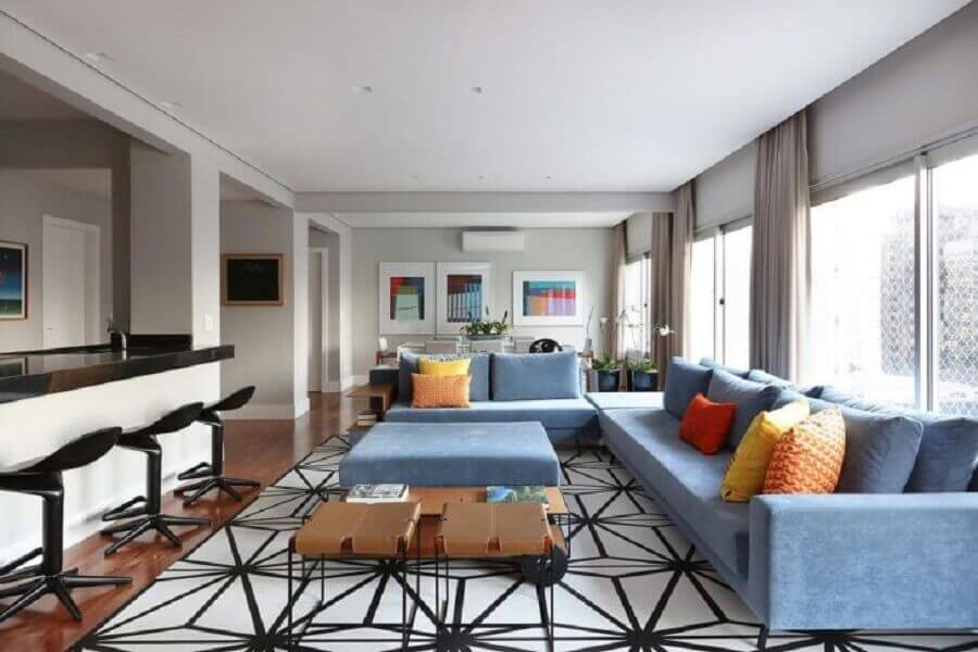 sala ampla decorada com sofá de canto azul claro e almofadas coloridas Foto Renata Popolo