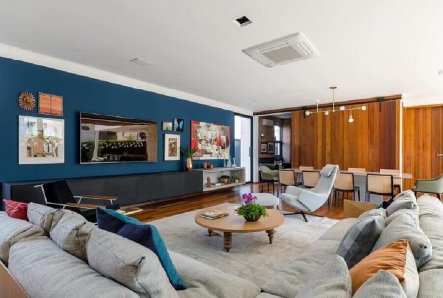 sala ampla decorada com sofá de canto e parede azul petróleo Foto Andrea Murao