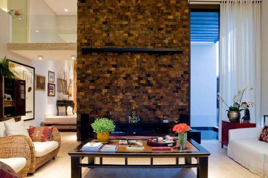 sala ampla e sofisticada decorada com poltronas de vime e revestimento pedra ferro Foto Pietre Colorate Rivestimenti