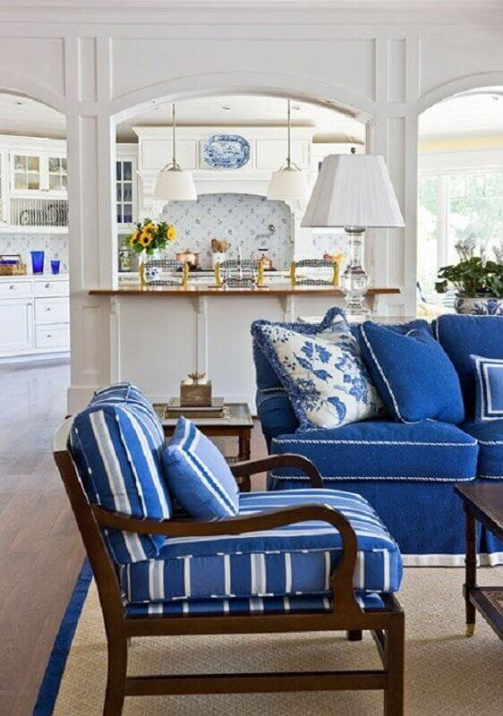 sala com sofá azul e poltrona de madeira Foto Decore com Gigi