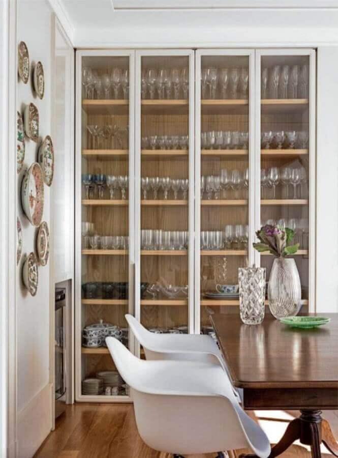 sala de jantar decorada com cristaleira branca com prateleiras de madeira Foto Elizabeth Martins