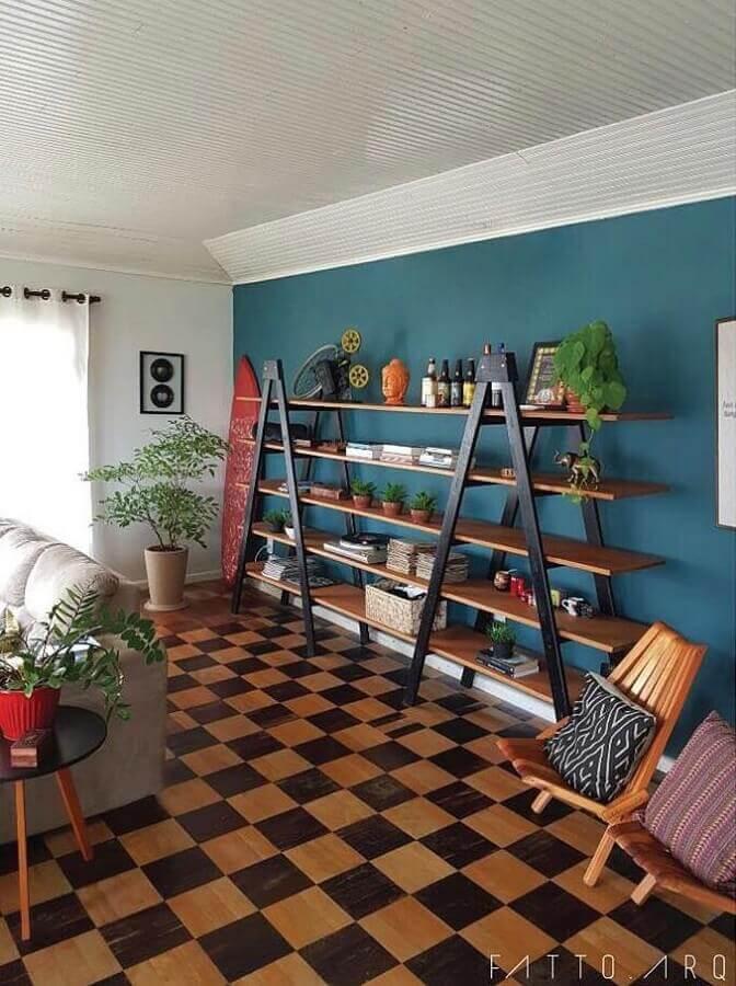 sala decorada com estante simples e parede azul petróleo Foto FATTO