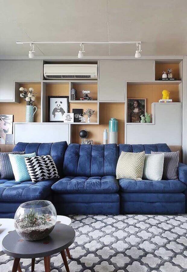 sala decorada com nichos de madeira e sofá retrátil azul Foto Mauricio Gebara Arquitetura