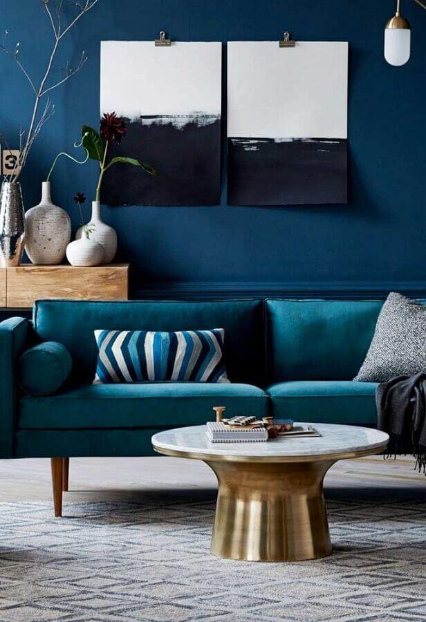 sala decorada com sofá azul petróleo e mesa de centro dourada Foto Boutique de décoration