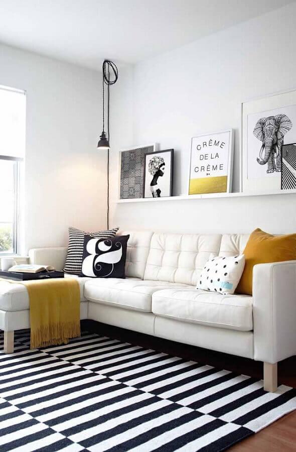 sala decorada com tapete listrado preto e branco e quadros tumblr