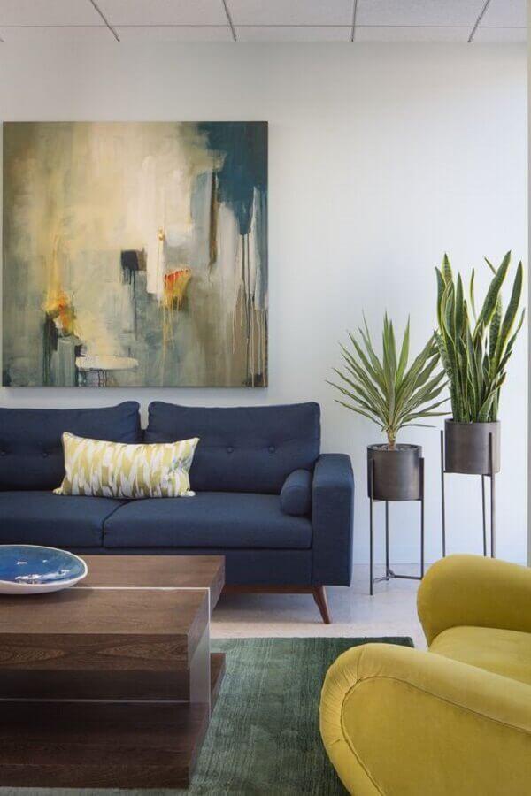 sofá azul escuro para sala decorada com quadro grande e vasos de chão  Foto Jeito de Casa