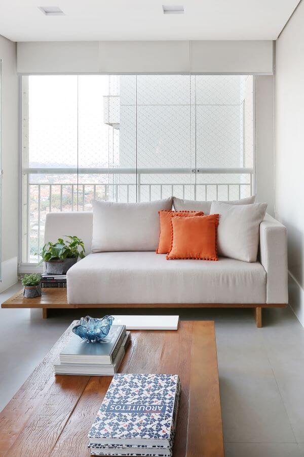 Sofá de madeira com almofada laranja