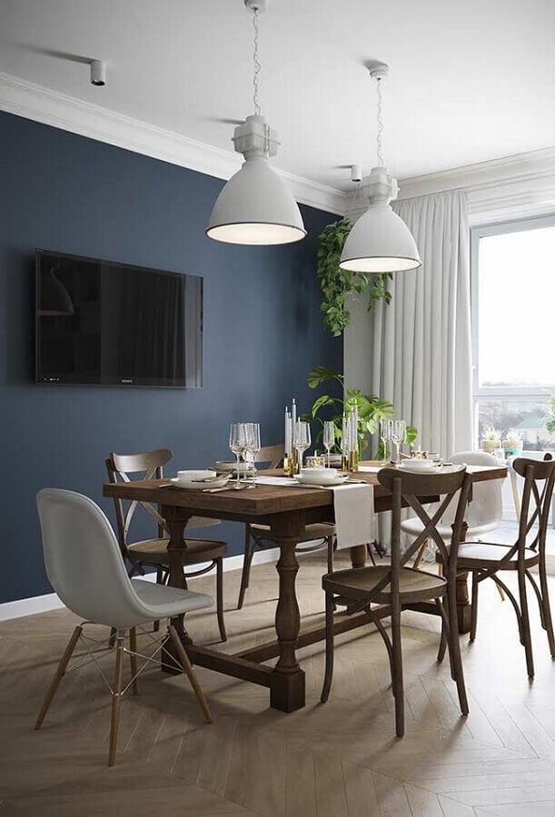 tinta de parede azul petróleo para sala de jantar com mesa de madeira e luminária branca Foto Behance