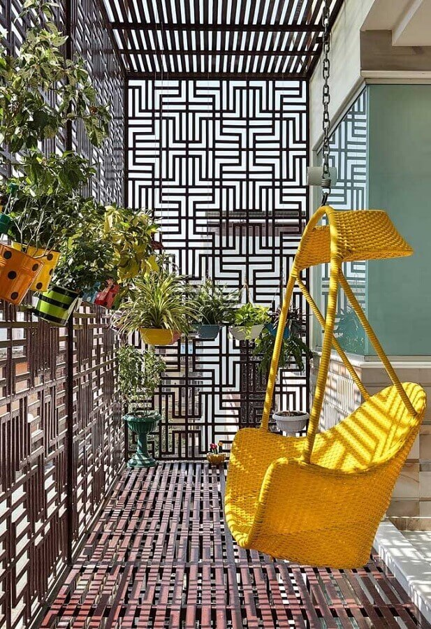varanda decorada com cadeira rattan amarela Foto Pinosy