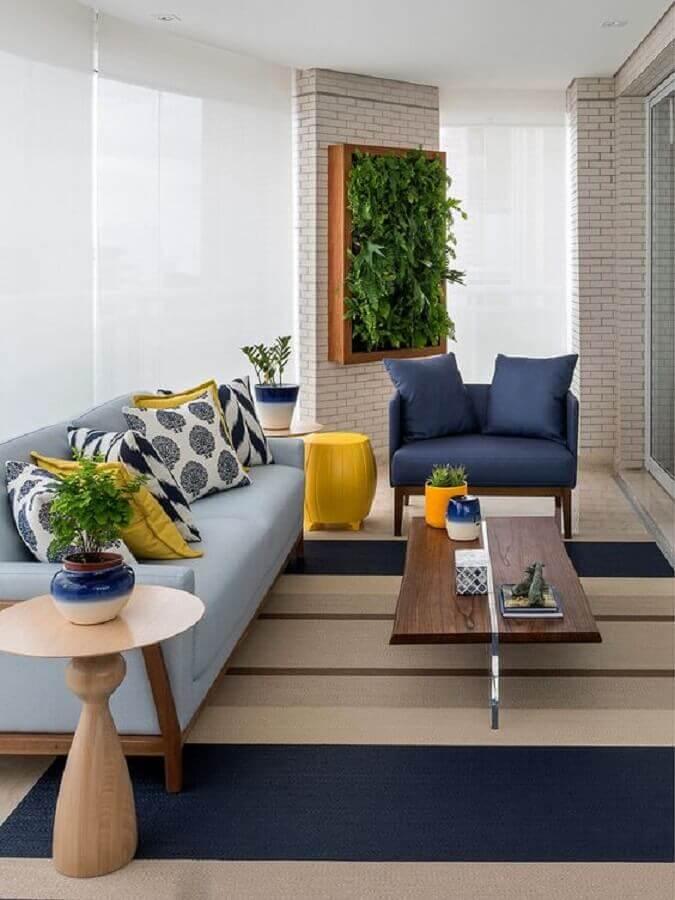 varanda decorada com tapete listrado e sofá azul claro  Foto Casa de Valentina