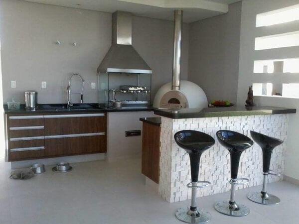 Área de lazer pequena com churrasqueira de vidro com coifa e forno de pizza