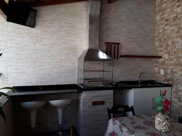 Área de lazer pequena com churrasqueira de vidro e bancada de granito preto