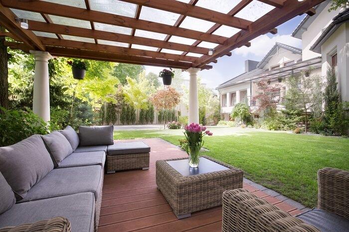 Área externa com varanda de madeira e sofá amplo com vários lugares