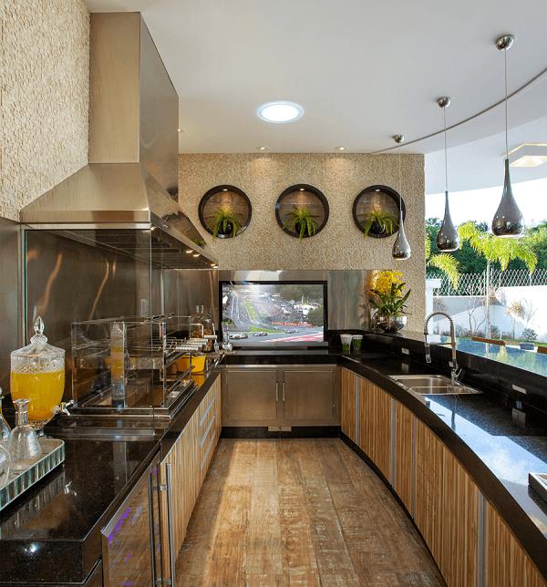 Área gourmet com churrasqueira de vidro e bancada de granito preta ampla