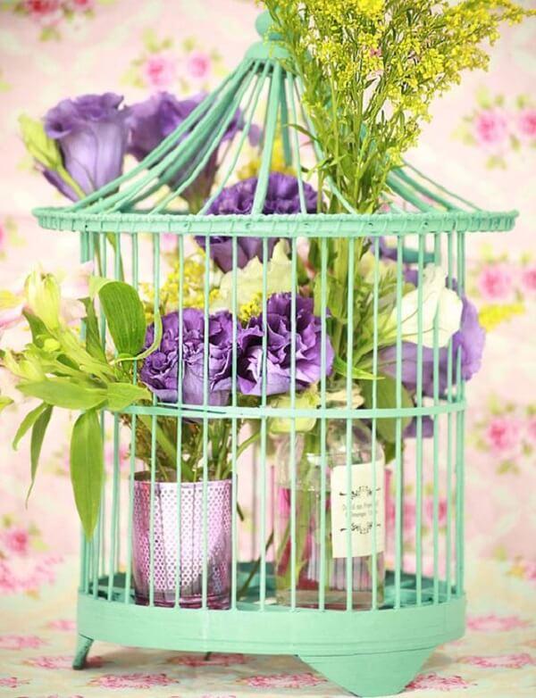 Gaiola decorativa verde com arranjo de flores