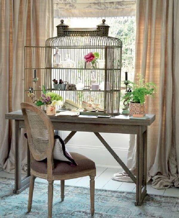 Gaiola decorativa serve de prateleira para escrivaninha de madeira