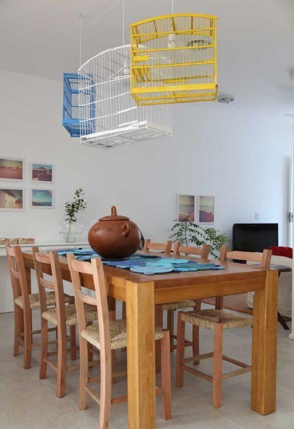 As gaiolas de passarinho foram utilizadas como luminárias na sala de jantar