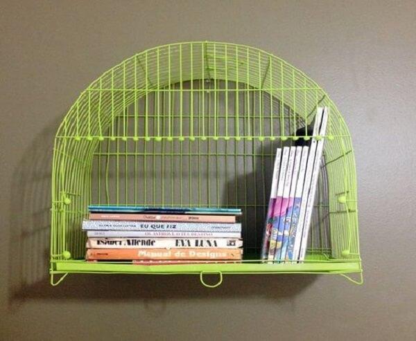 Gaiola decorativa verde serve de prateleira para livros