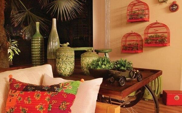 Gaiolas decorativas penduras na parede servem de base para vasos de plantas