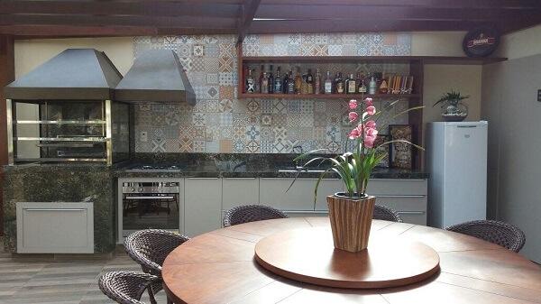 Área de lazer aconchegante com mesa de madeira redonda e parede revestida com ladrilhos hidráulicos
