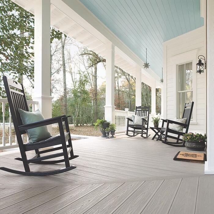 A entrada da casa conta com uma varanda de madeira clean e cadeiras de balanço