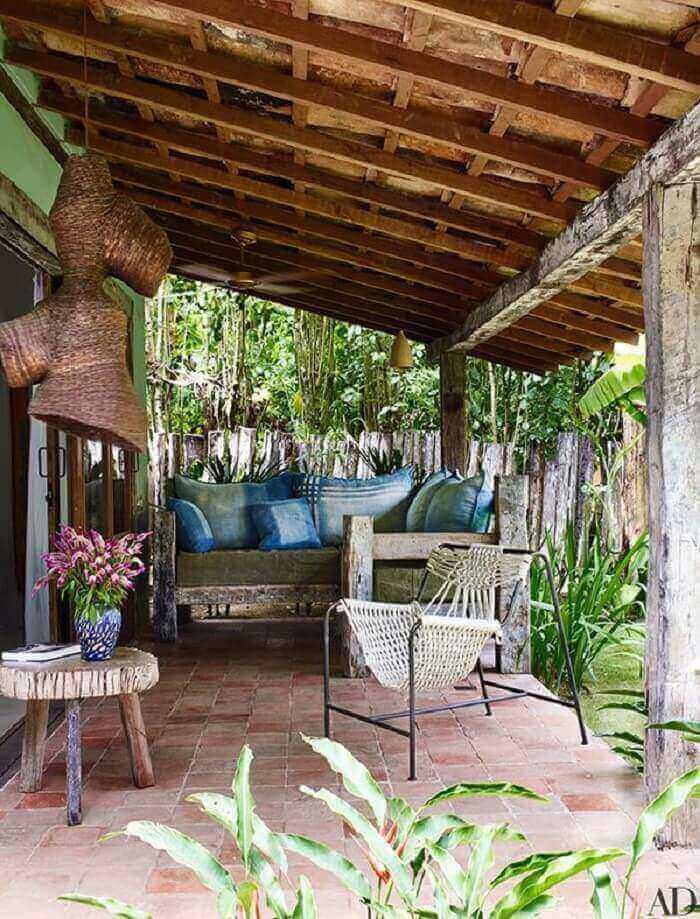 A varanda de madeira se integra ao paisagismo local