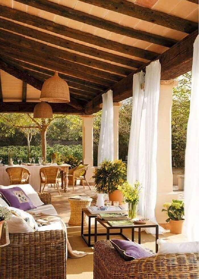 As cortinas brancas minimizam a entrada de luz solar na varanda de madeira