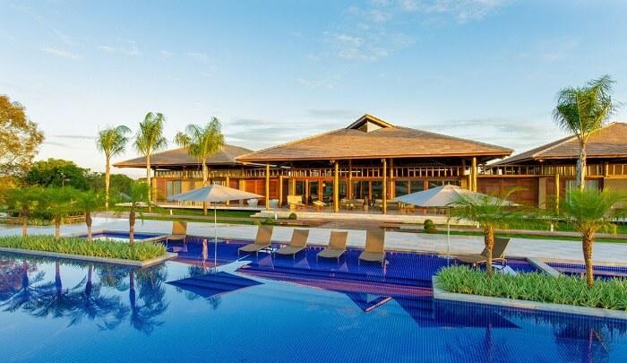 Casa de madeira com varanda conta com a presença de piscina e paisagismo encantador