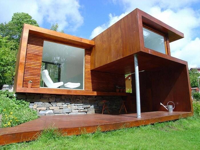 Casa de madeira com varanda. Arquitetura moderna e parede com pedras naturais