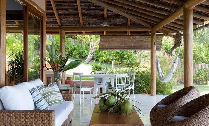 Casa de praia com varanda de madeira, móveis rústicos e rede para descanso
