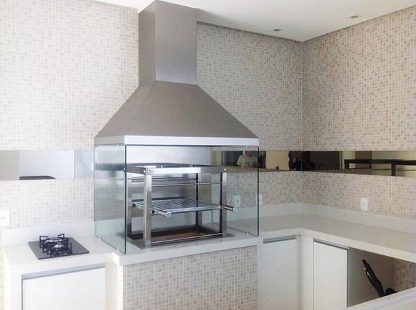 Churrasqueira com coifa de inox e lateral de vidro instalada ao lado do cooktop