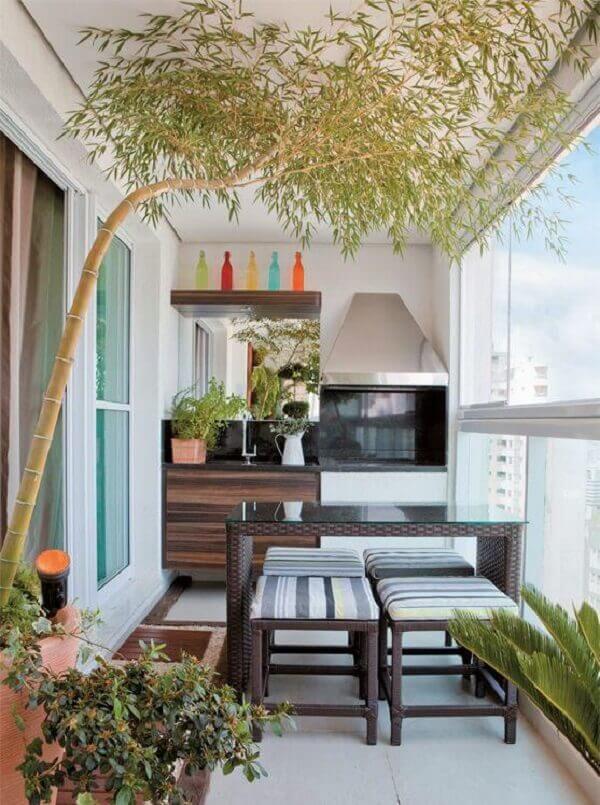 Varanda gourmet de apartamento conta com a presença de uma churrasqueira de vidro