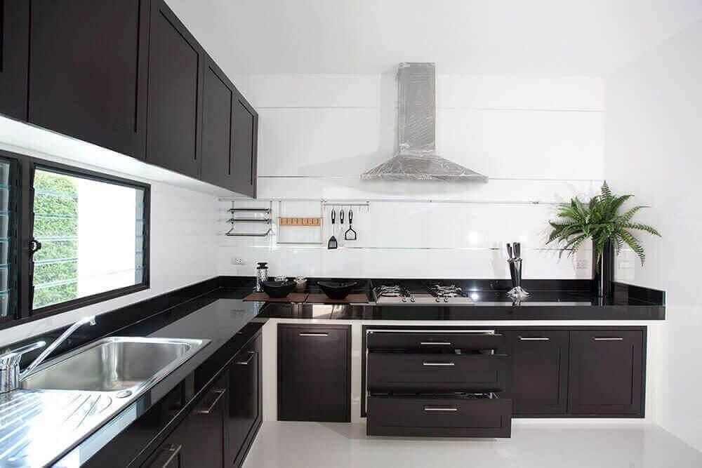 Cozinha em formato L feita com bancada de granito preto