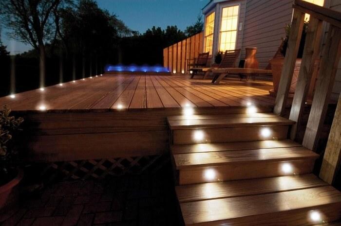 Entrada com varanda de madeira e iluminação especial do jardim