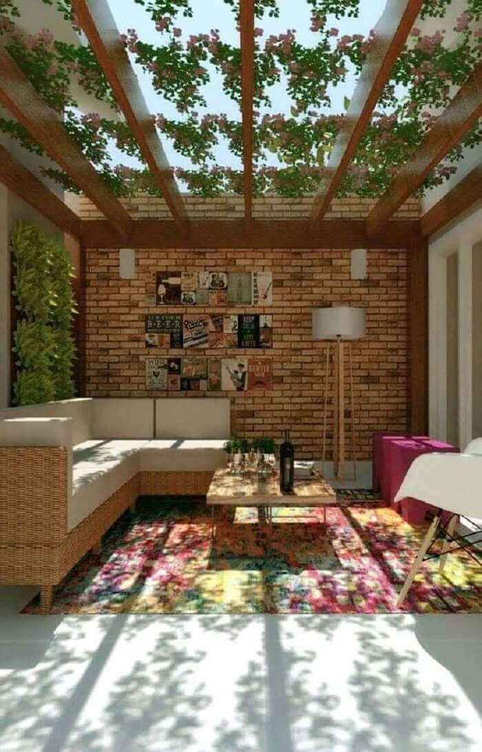 Espaço contempla varanda de madeira com parede de tijolinho