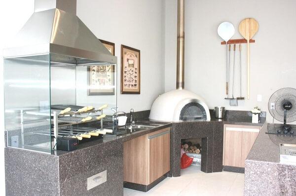 Espaço gourmet com churrasqueira de vidro e bancada de granito preto