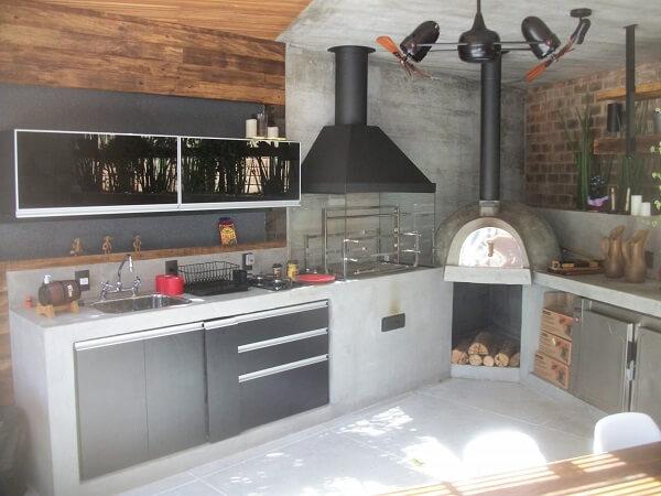 Espaço gourmet de uma casa conta com a presença de uma churrasqueira de vidro e forno a lenha