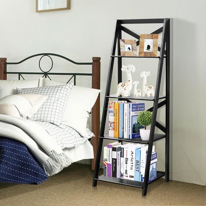 Estante escada preta posicionada ao lado da cama de casal facilita o acesso de diversos itens
