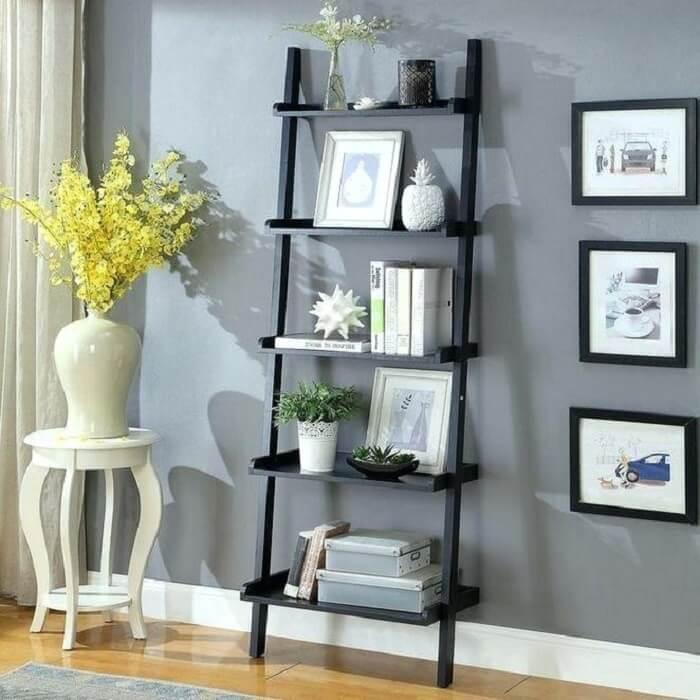 Estante escada preta serve de apoio para itens decorativos da sala de estar