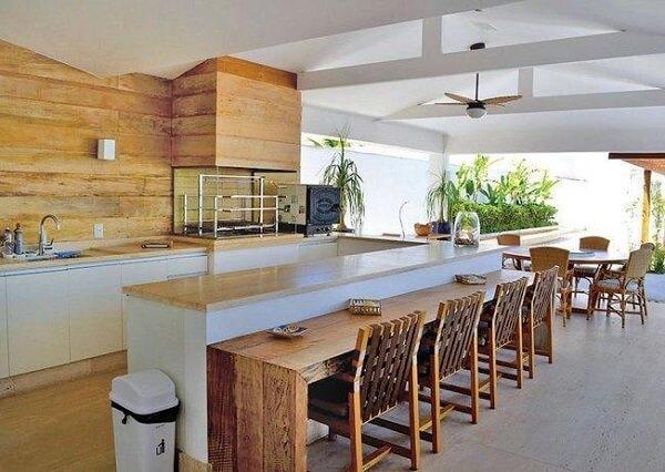 Espaço gourmet para reunir família e amigos com bancada de madeira extensa