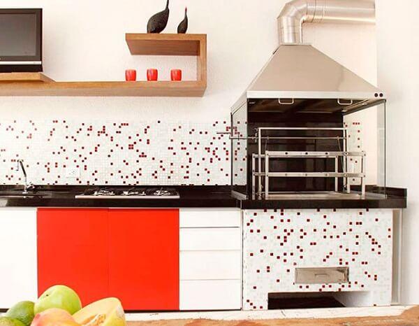 Pequena área gourmet com cooktop e churrasqueira de vidro