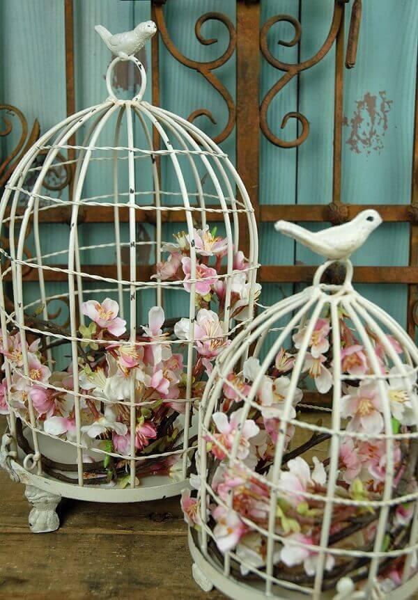 Gaiolas decorativas na cor branca servem de apoio para as flores