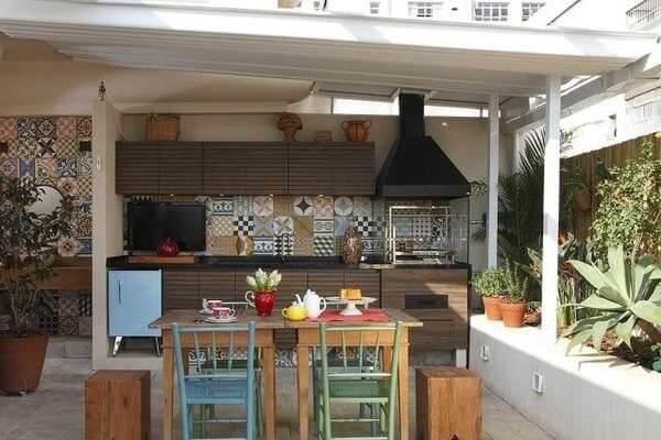 Área de lazer pequena com móveis em madeira e churrasqueira de vidro