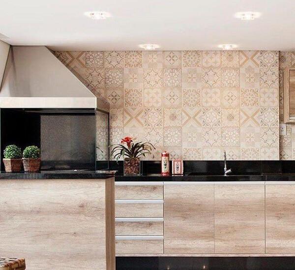 Churrasqueira com coifa de inox e laterais de vidro instalada no canto da parede da área gourmet