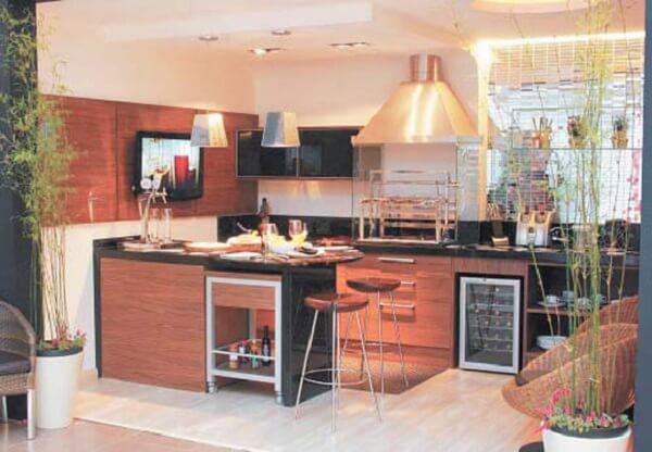Área de lazer pequena com pendentes metálicos, banquetas, adega embutida e churrasqueira de vidro